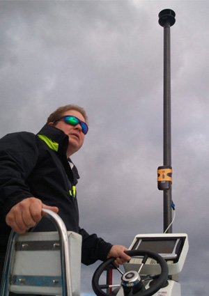 WindBot true wind measuring system mounted on a boat with sailor in foreground